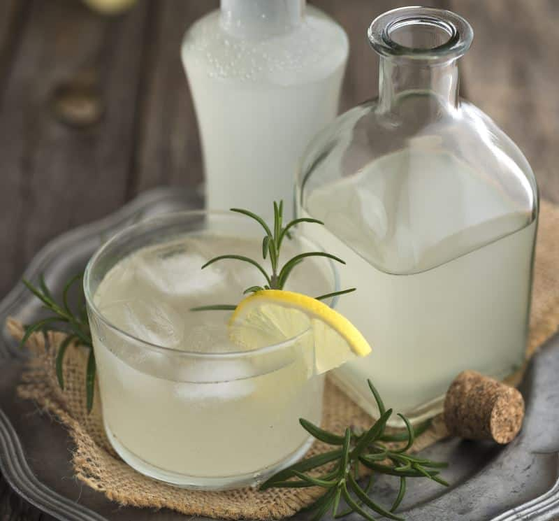 A glass of ginger beer with rosemary and lemon on a silver tray.