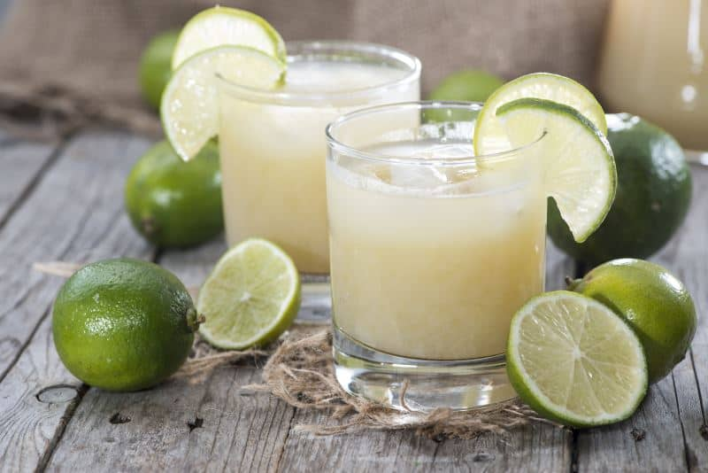 Fresh-squeezed lime juice in glasses with whole limes on a wooden table.