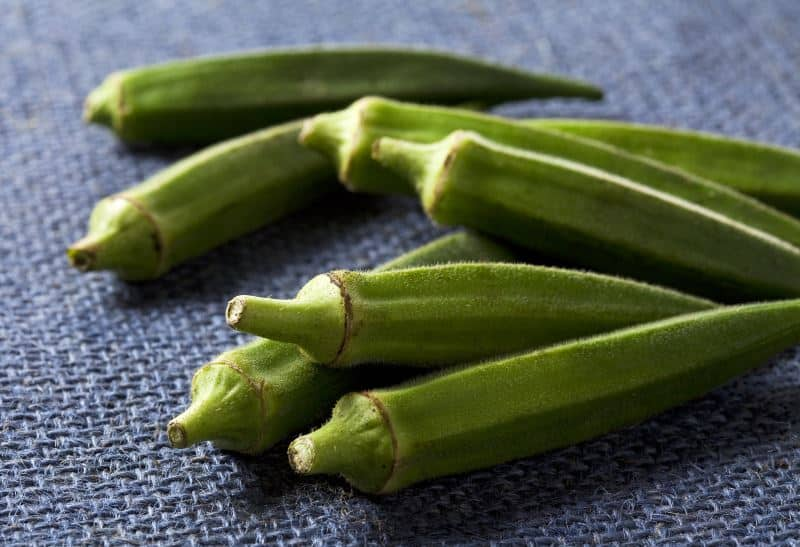 Fresh okra on a fabric mat.