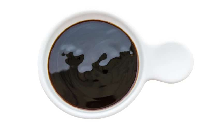 A close-up of oyster sauce in a white saucer against a white background.