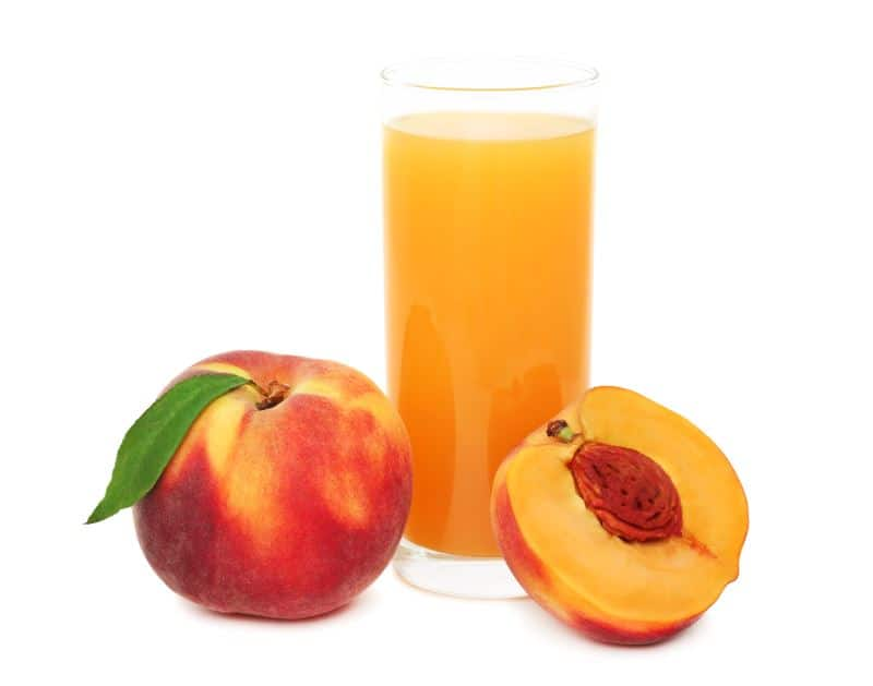 A glass of peach juice with fresh peaches on a white background.