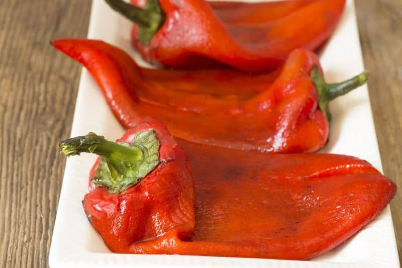 Peeled roasted red peppers on a white plate