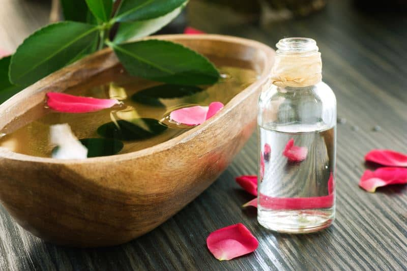 Rose water in a bottle and in a wooden bowl with rose petals.