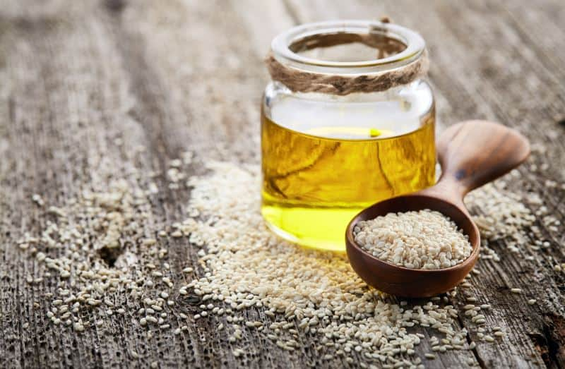 A glass jar of sesame oil next to a wooden spoon on top of a heap of sesame seeds on a wooden surface.
