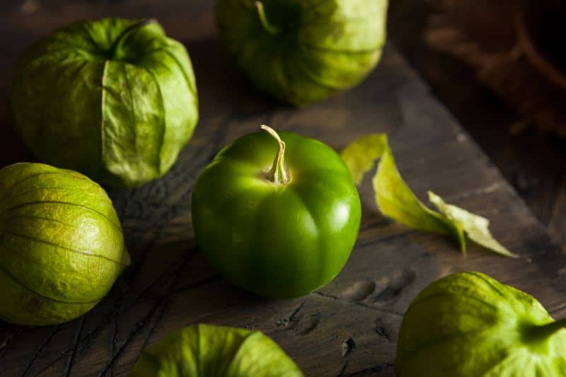 Fresh tomatillos on a wooden table.