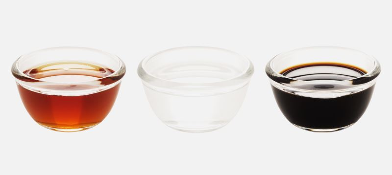Red wine vinegar, white vinegar and balsamic vinegar in glass bowls against a white background.