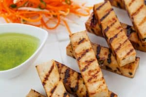 tofu with green sauce and carrots on a place