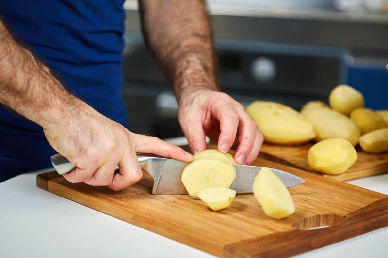 Man chopping peeled potatoes on a wooden cutting board
