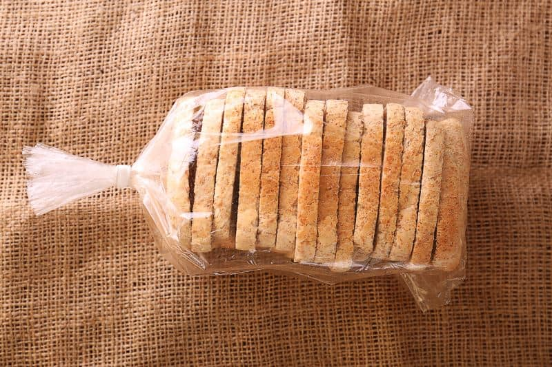Sliced bread in plastic bag on a burlap sack on sackcloth, top view