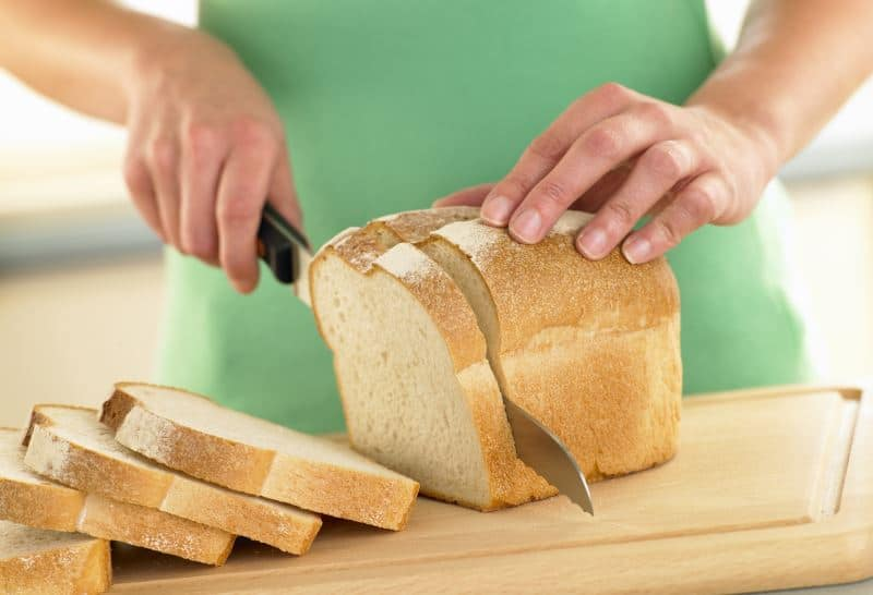 Woman slicing a loaf of white bread on a cutting board