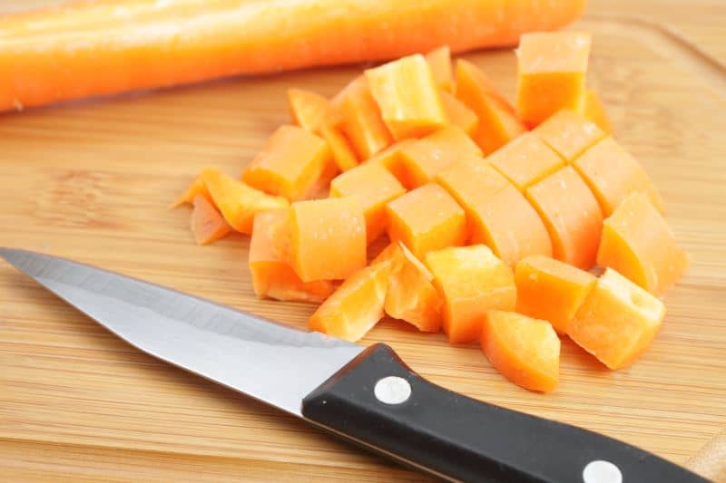 Diced carrots next to a knife on a cutting board