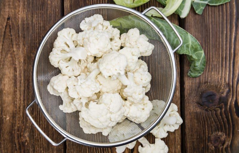 Cauliflower florets in a mesh colander