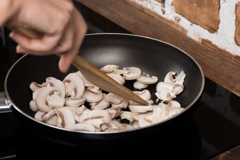 Sauteing mushrooms in a pan with a wooden spoon