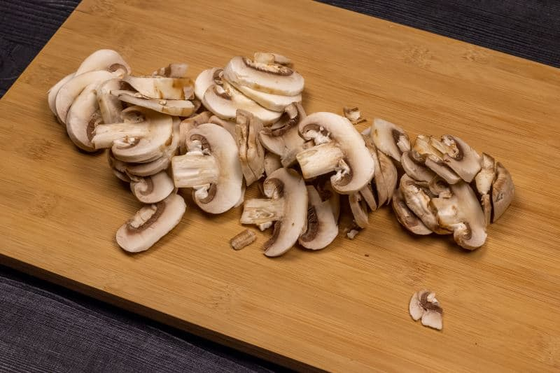Sliced mushrooms on a wooden cutting board