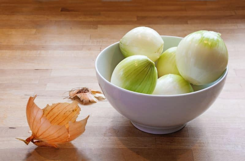 Peeled onions in a bowl on a wooden counter