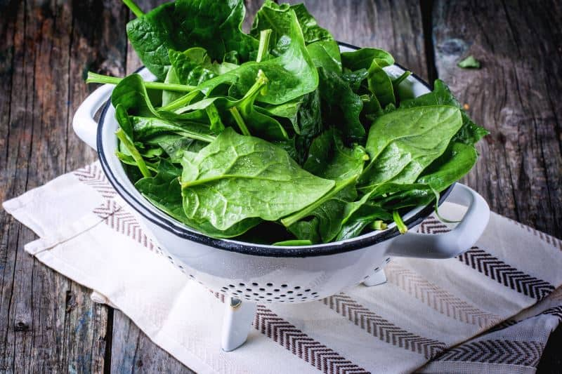 Spinach drying in a colander over a kitchen towel
