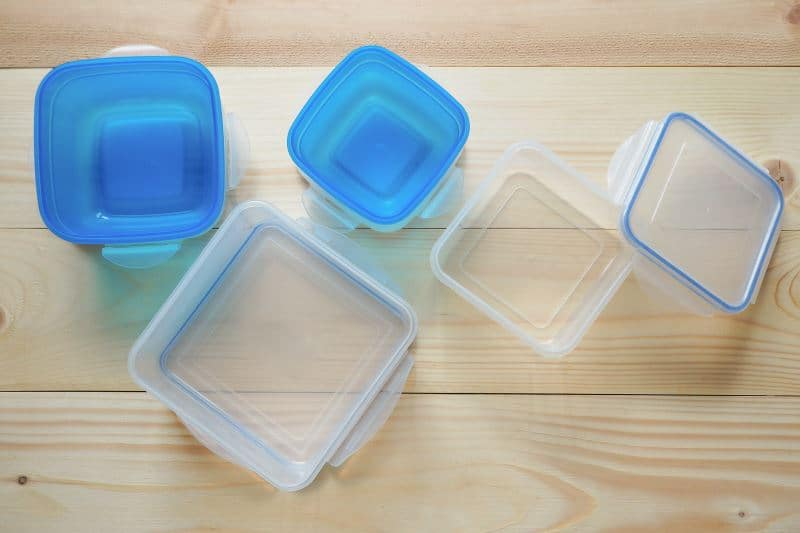 Tupperware with blue lids on a wooden table