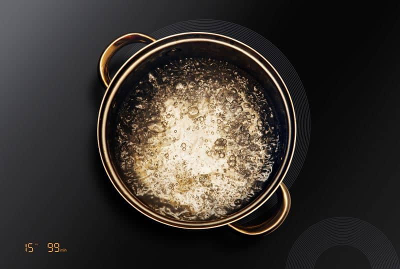 Water boiling on a black stove top